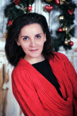 avantegarde: Portrait of beautiful dark-haired woman in a red dress on a background of Christmas decorations  Stock Photo