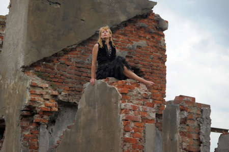 woman in black sitting on the ruins photo