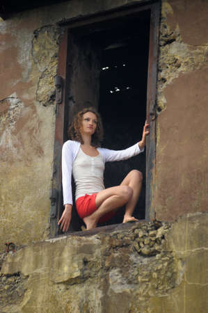 young woman in the window of a ruined house Stock Photo - 25817102