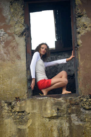 young woman in the window of a ruined house Stock Photo - 25817113