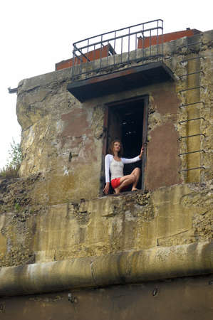 young woman in the window of a ruined house Stock Photo - 25817116