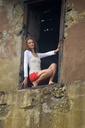 young woman in the window of a ruined house photo
