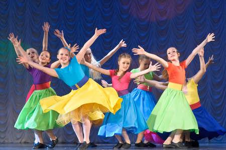 meisjes dansen in kleurrijke jurken op het podium Redactioneel