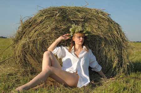 Young woman on the field with big hay bale rolls  photo