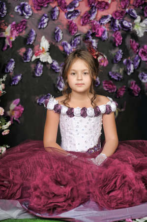 Girl in a purple dress on a floral background.