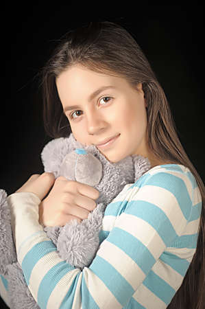 Beautiful young brunette girl with teddy bear. photo