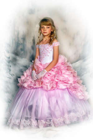 niños vistiendose: Cute girl in a pink princess dress on winter background in studio. Foto de archivo