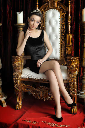 Fashion and glamour concept - sexy woman in crown and black dress sitting in throne. Imagens