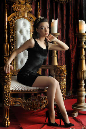Fashion and glamour concept - sexy woman in crown and black dress sitting in throne. Stock fotó