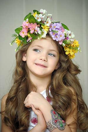 Mooi meisje dragen van een krans van bloemen en een armband op haar arm, studio foto
