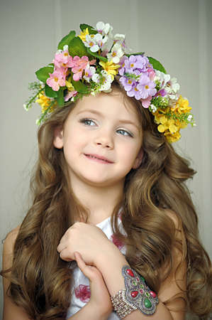 Beautiful little girl wearing a wreath of flowers and a bracelet on her arm, studio photo