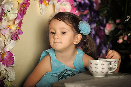 Beautiful Little girl in a smart dress around the table with tea and marshmallow  photo