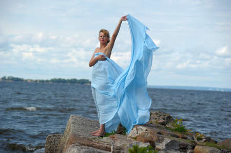 woman in blue on the rocks by the sea photo