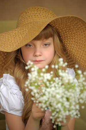 Girl in a straw hat with a bouquet of lilies of the valley photo