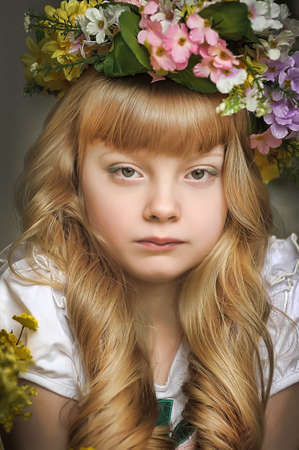 enjoymant: Beautiful young blond girl in a wreath of flowers Stock Photo