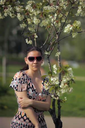 Woman in sunglasses near the flowering branches photo