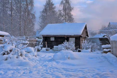 specific: Winter rural scenery. Wooden house and trees covered with snow. Christmas and seasonal specific concept.