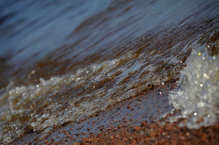 frothy: Frothy ocean wave on a sandy beach