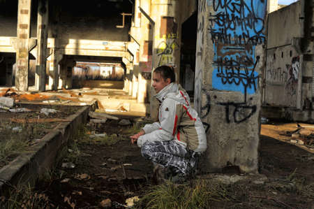 Girl in abandoned, run-down industrial building interior. photo