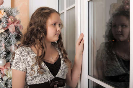 Teen girl looking out the window  photo