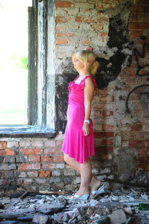 Young woman in pink dress among the ruins of an abandoned burned house. photo