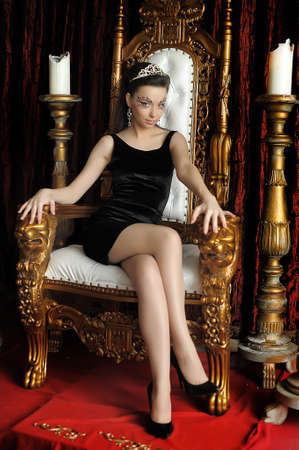 Fashion and glamour concept - sexy woman in crown and black dress sitting in throne. photo