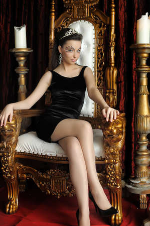 Fashion and glamour concept - sexy woman in crown and black dress sitting in throne. Stock Photo