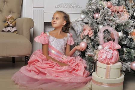 Smart girl in a pink dress in Christmas. Stock Photo
