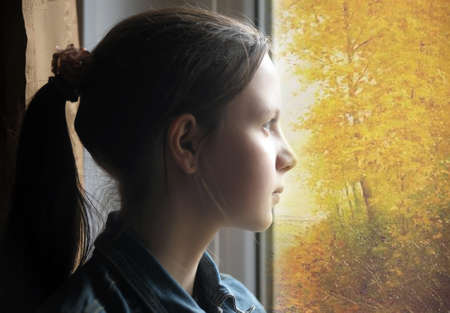 Teen girl looking out the window at the autumn landscape. photo