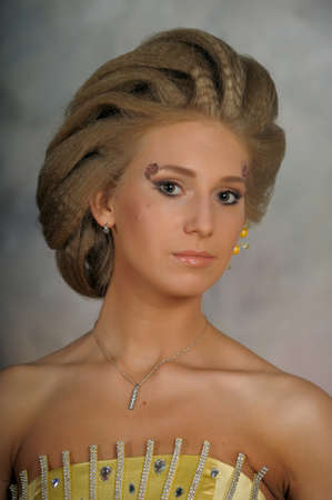 Girl with creative hairstyle and yellow dress with sequins. photo