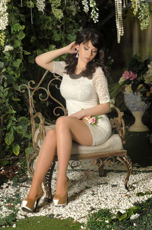 slender brunette in a white dress in the garden among the flowers photo