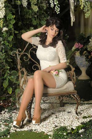 slender brunette in a white dress in the garden among the flowers photo