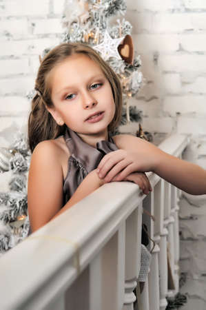 Pretty young girl dreaming of Christmas with a sparkling Christmas tree behind. photo