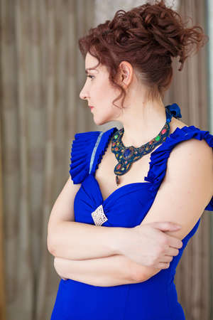Portrait of elegant woman in stylish blue dress and elaborate necklace, looking relaxed Stock Photo - 29349957