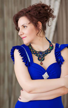 Portrait of elegant woman in stylish blue dress and elaborate necklace, looking relaxed    photo