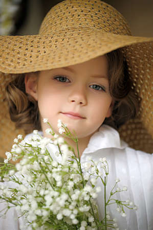 Girl in a straw hat with a bouquet of lilies of the valley. photo
