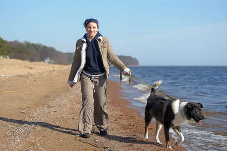 Young woman with a dog walks along the sea. photo