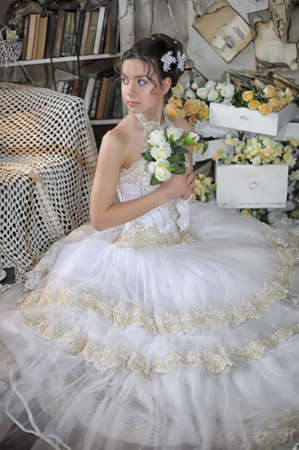 Beautiful young bride in a wedding dress in vintage interior photo