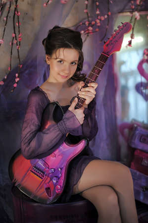 Beautiful young girl with electric guitar photo