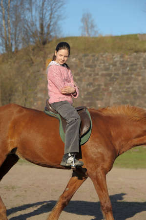 Girl riding on the brown horse. photo