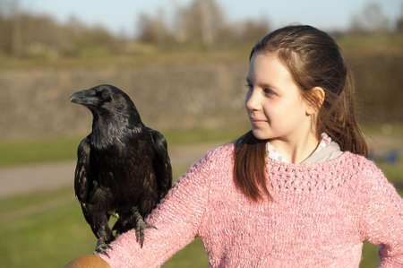 Girl with raven on his shoulder. photo
