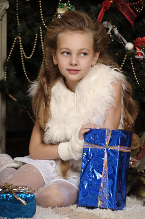 Girl with a gift in blue packaging in the Christmas tree. photo