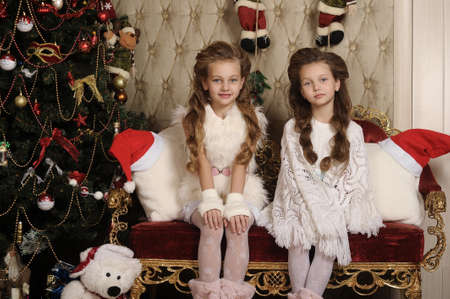 two girls sisters in a Christmas interior photo