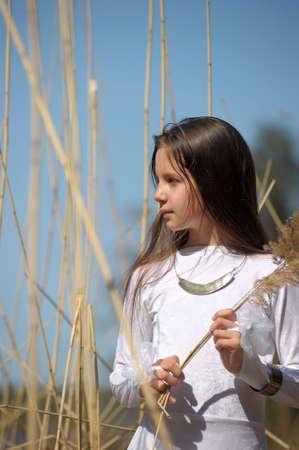 Girl in white dress among the high dry grass. photo