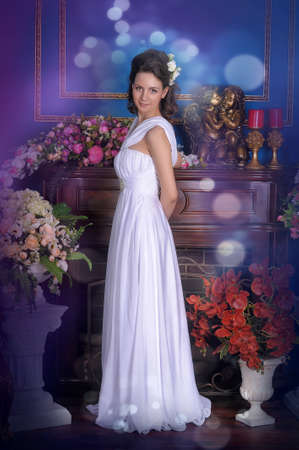 Exquisite elegant girl in white dress among the flowers  photo