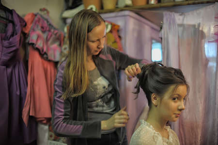 snips: Stylist makes hair model in the dressing room.