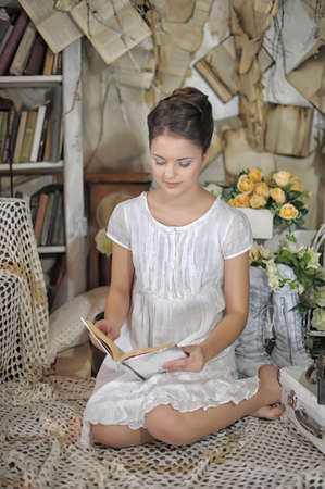 Young girl in a vintage dress. reading a book