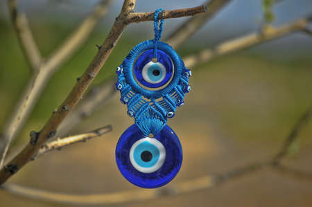 Evil eye charms hang from a bare tree in Cappadocia, Turkey.