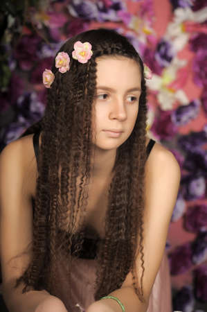 Long-haired brunette girl with flowers in her hair. photo