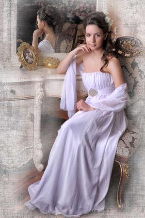 Vybrané elegantní dívka v bílých šatech sedí na židli u zrcadla.